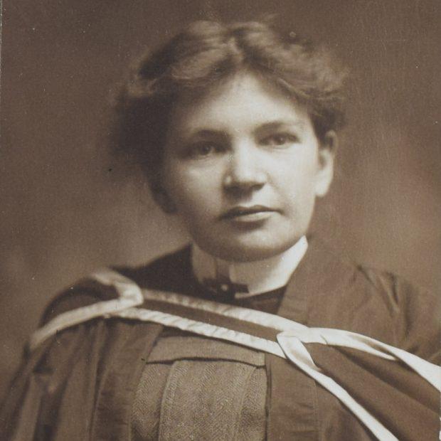 Photographie en noir et blanc de Maude Abbott, jeune adulte, tête et épaules. Elle porte un habit et une toge de graduation. Ses cheveux foncés sont attachés à l'arrière de sa tête et sa tête est légèrement tournée vers la gauche.