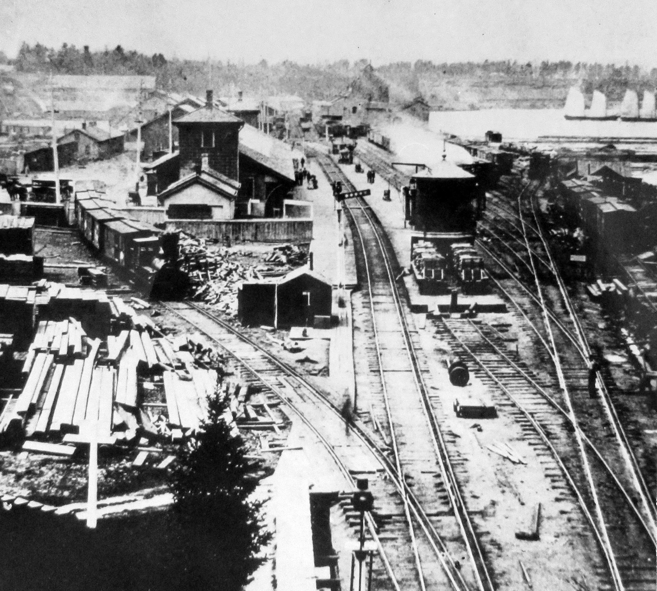 Wagons alignés d'un côté de la gare de triage de la Great Western Railway. On voit aussi sur l'image des piles de bois et d'autres matériaux sur les voies. Deux travailleurs se trouvent à l'avant-plan.