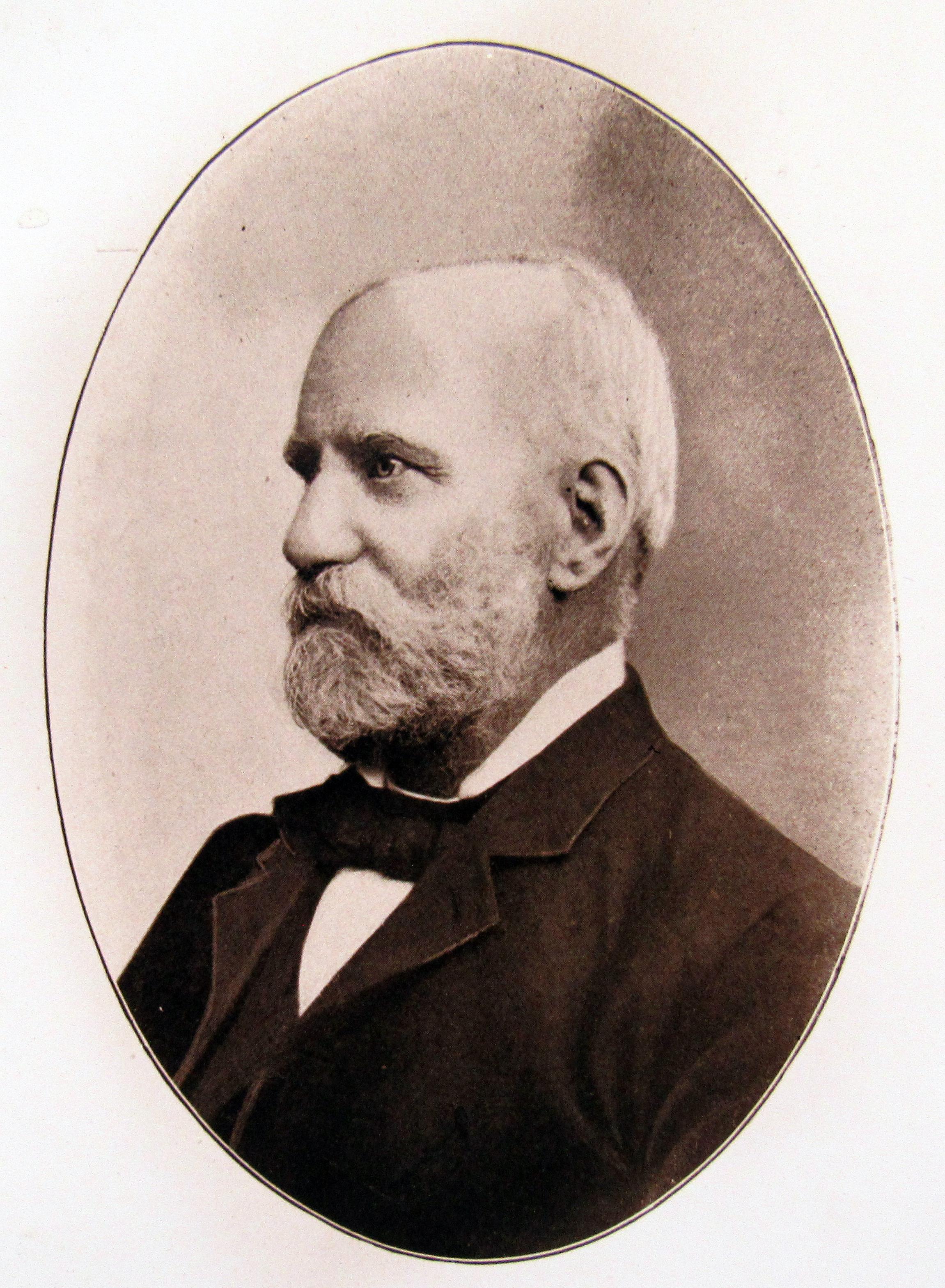 Photographie sépia de H. B. Witton prise plus tard dans sa vie. On y voit l'homme en tenue formelle, portant une barbe blanche bien taillée. Le portrait est pris de profil.