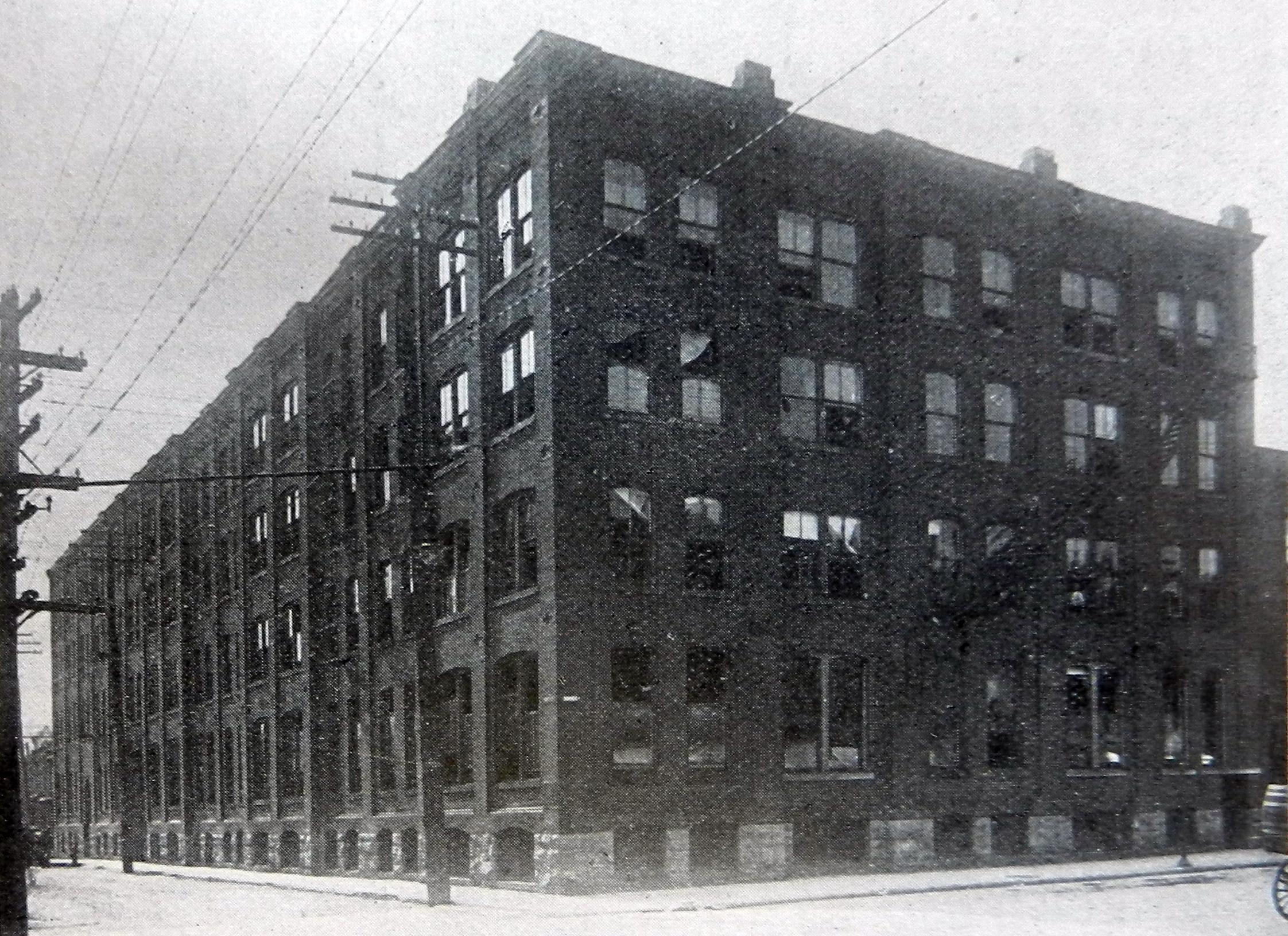 Photographie de l'usine de quatre étages de John McPherson, occupant près d'un pâté de maisons complet.