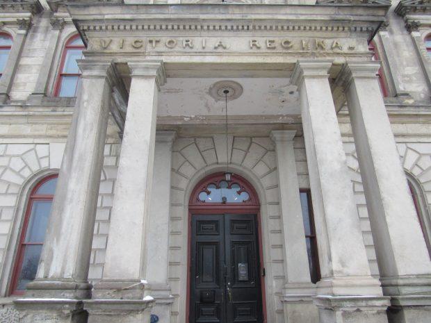 Entrée d'un bâtiment à deux étages. La porte est flanquée de deux piliers de chaque côté; le haut du portique porte l'inscription en latin « Victoria Regina »