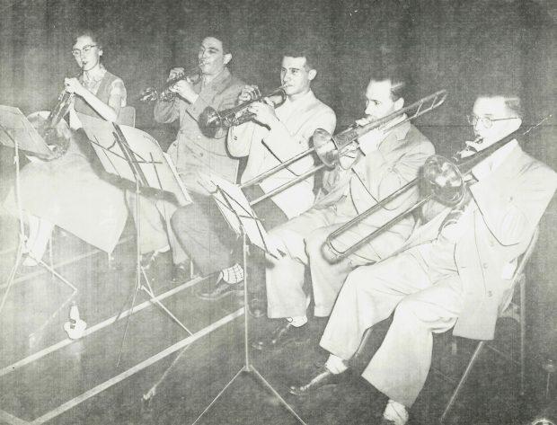 Cinq joueurs de cuivres en répétition