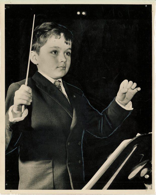 Un jeune garçon portant un costume porte une baguette dans un main et tient des gestes avec l'autre main