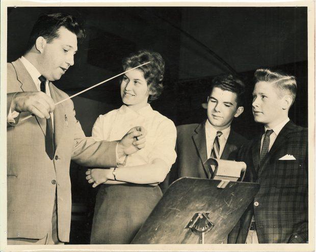 Leonard Pearlman démontre aux trois étudiants comment diriger un orchestre