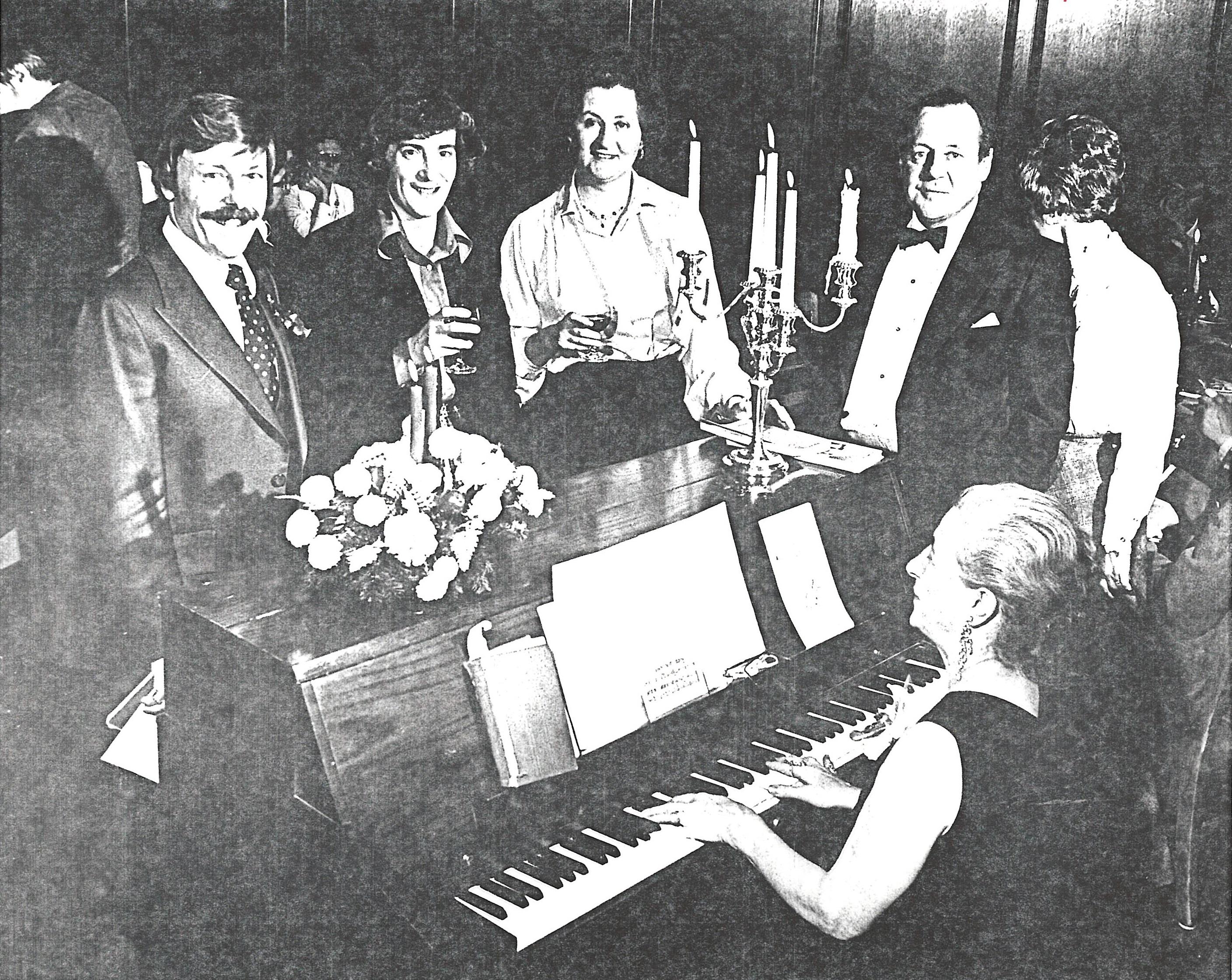 Quatre membres du conseil d'administration s'interposent près d'un piano durant une soirée