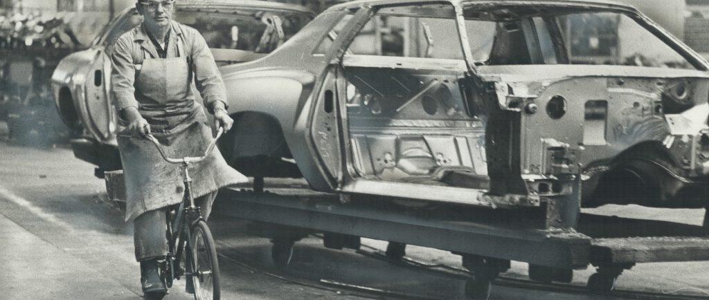 Image en noir et blanc représentant un homme portant un tablier et une casquette de baseball à l'envers roulant à vélo à côté d'une voiture inachevée sur une chaîne de montage.
