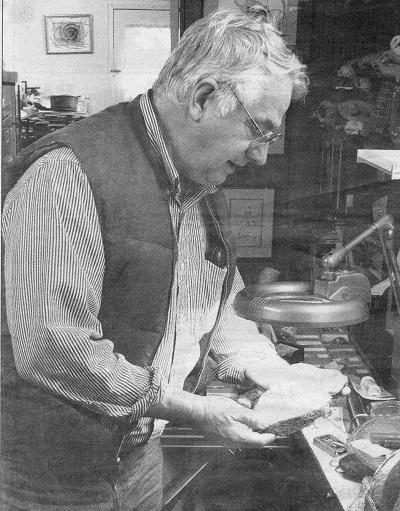 Graham Beard, chez lui, regardant un fossile sous une lampe. c. 1995