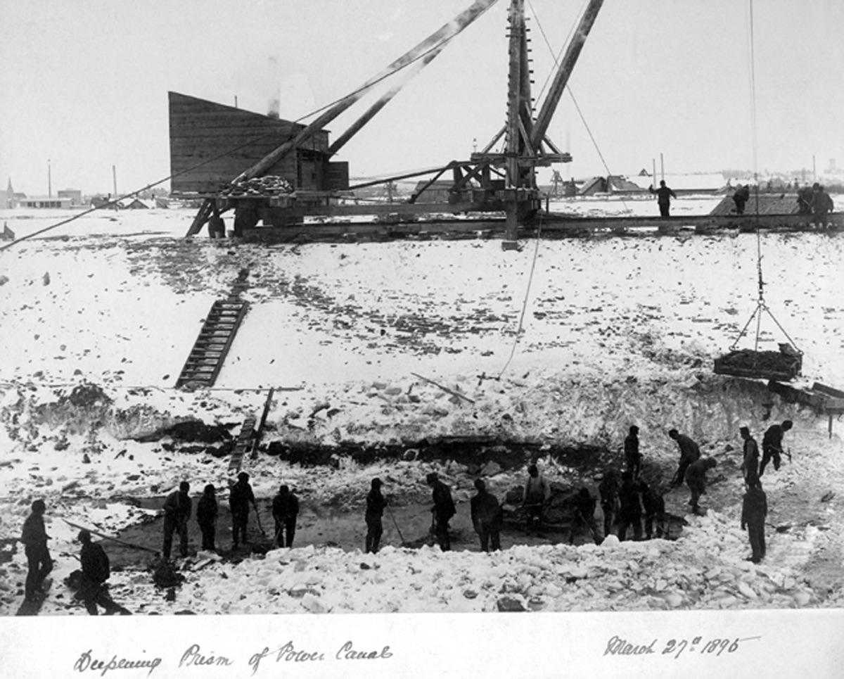 On aperçoit ici des ouvriers creusant un trou géant lors de la construction du canal hydroélectrique en plein hiver.
