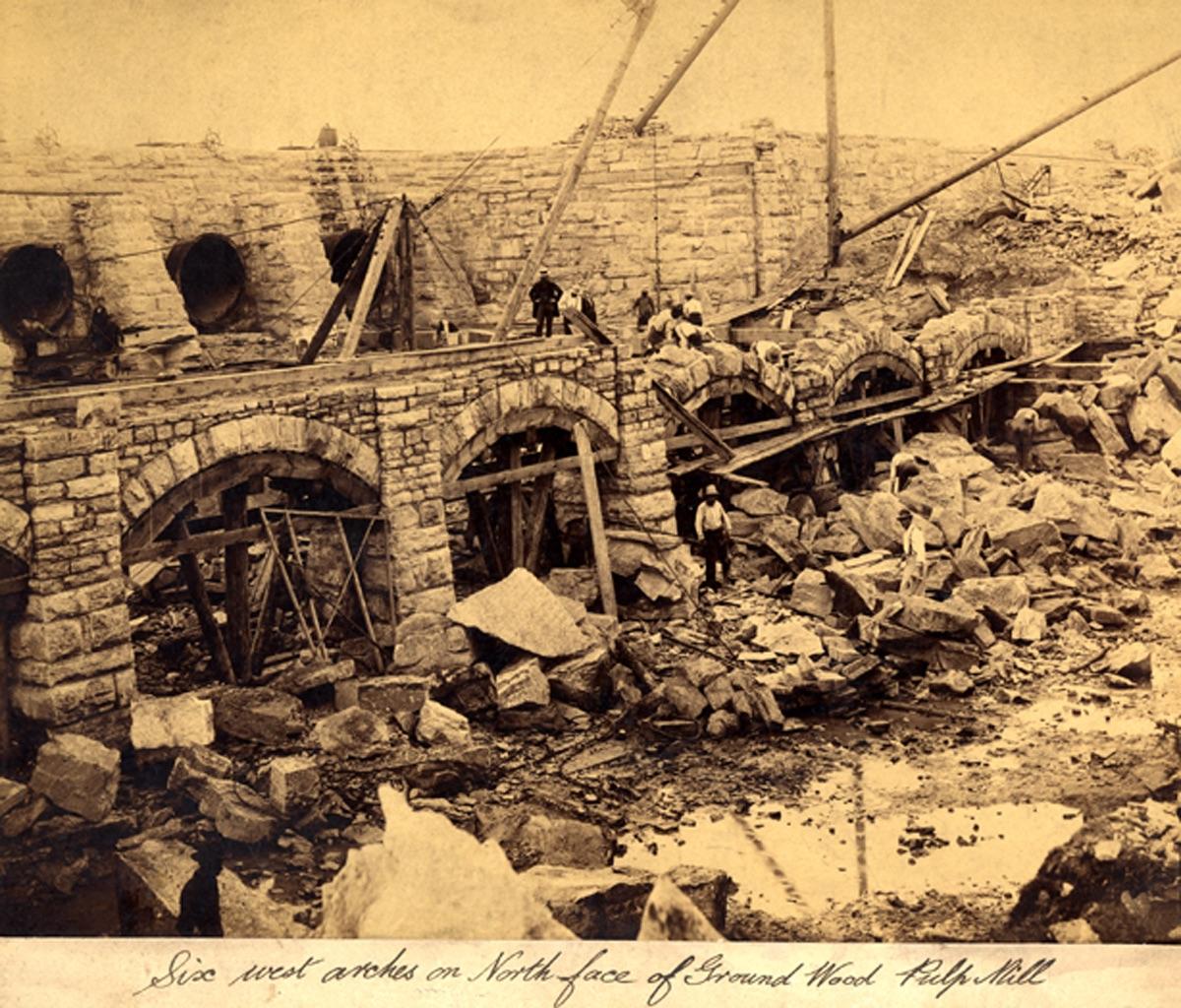 Construction d'arches en grès. Scène animée avec grues, pierres et travailleurs.
