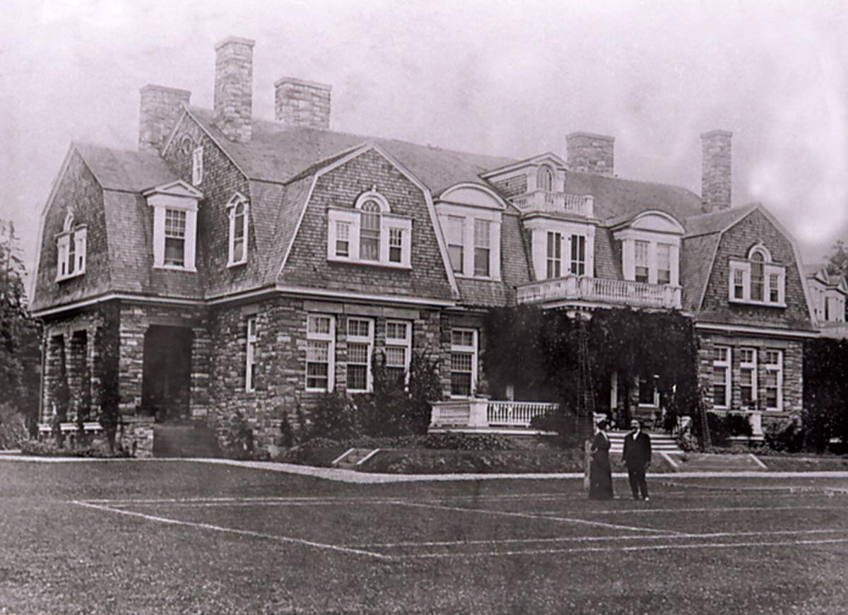 Deux personnes se tiennent debout dans le parterre devant le manoir en pierre de grès construit sur une colline.