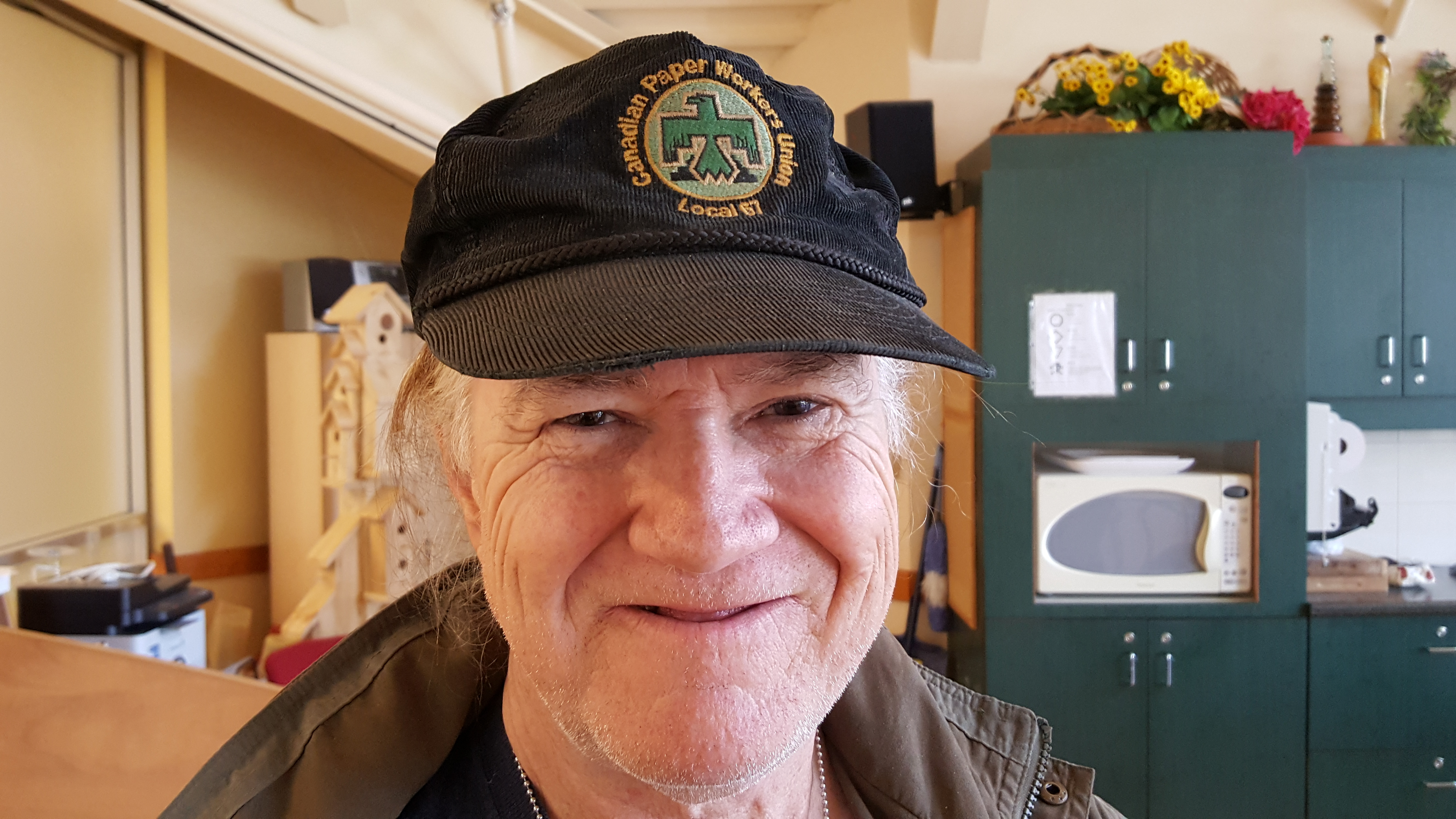 Retraité de l'usine à papier portant une casquette de la 'Canadian Paper Workers Union'. Il se tient debout, souriant, dans la salle de réunion à la mezzanine de l'épicerie Rome's.