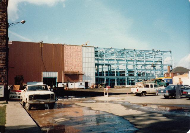 Structure d'acier érigée sur un des côtés du nouvel édifice; l'autre façade à gauche est recouverte d'un parement. Des camions sont présents et un écriteau appuyé sur l'atelier d'usinage indique «chantier de construction».