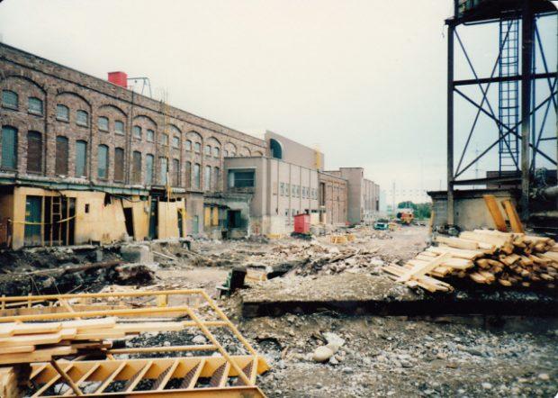 Chantier de construction, atelier d'usinage à gauche, gravier et poutres de bois à l'avant plan.