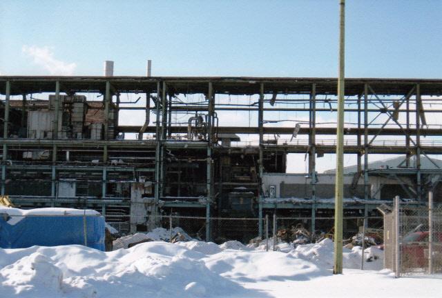Les poutres de l'un des édifices modernes sont mises à nu durant la démolition. On aperçoit la neige en avant plan. Le bâtiment a des allures décrépites.