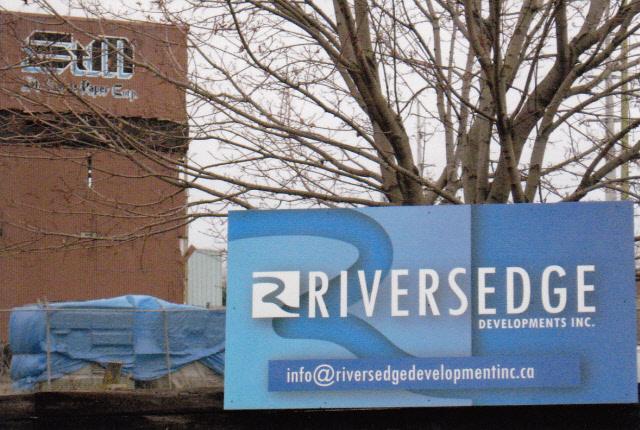 Photo de l'enseigne de Riversedge Developments Inc. sur la clôture de la propriété de la St. Mary's Paper Corp.