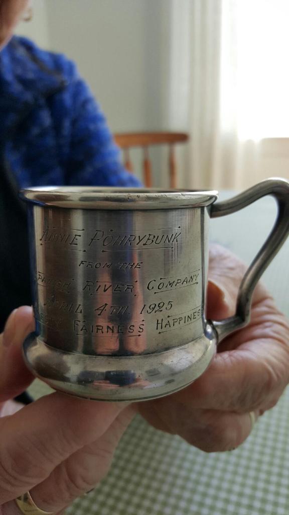 Deux mains de vieille femme qui tiennent une petite tasse en argent portant l'inscription: «To Annie Pohrybunk, April 4, 1925 from the Spanish River Company».