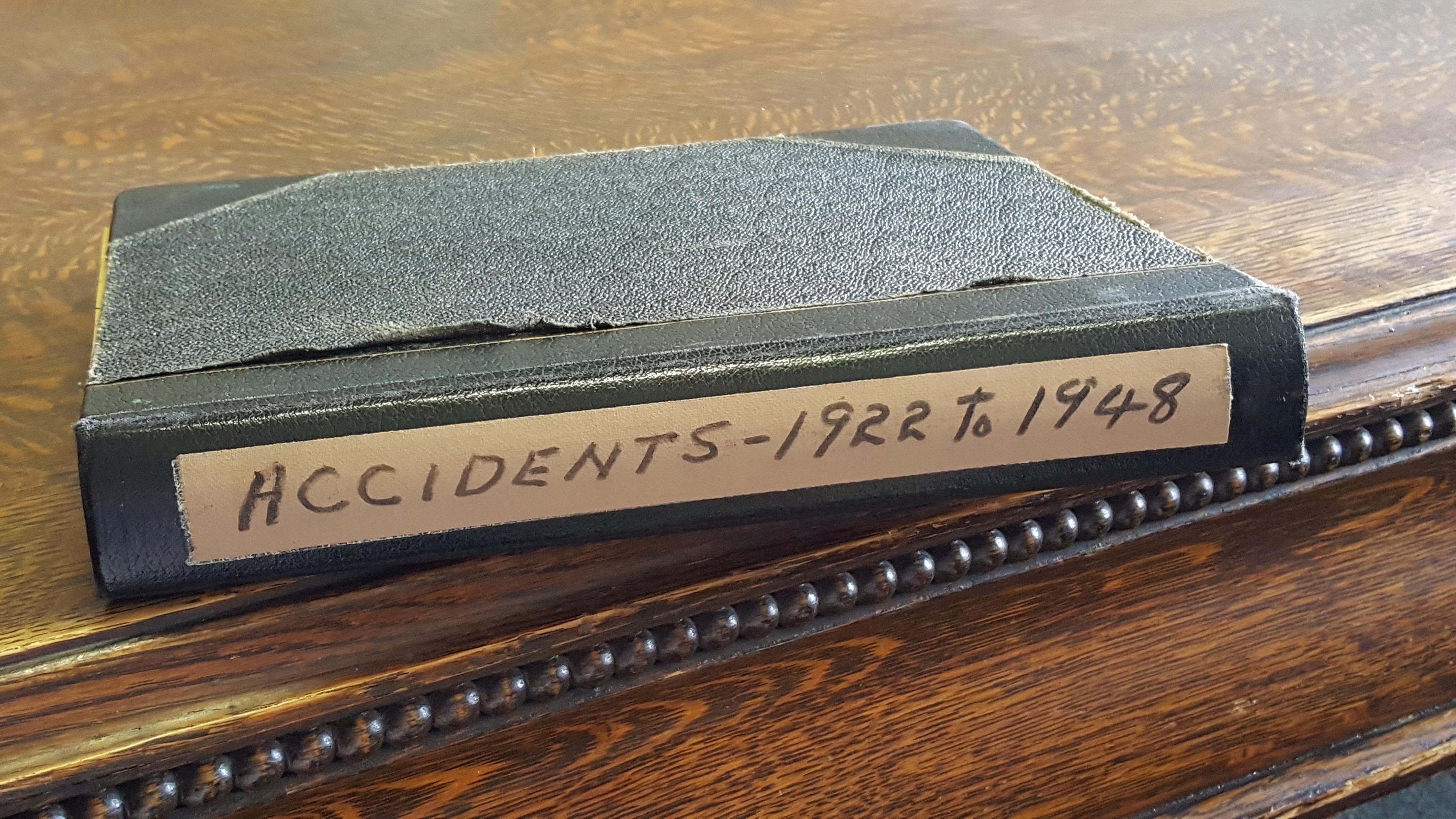 Vieux carnet noir sur une table en bois. Sur une étiquette au dos du livre est inscrit: Accidents – 1922-1948