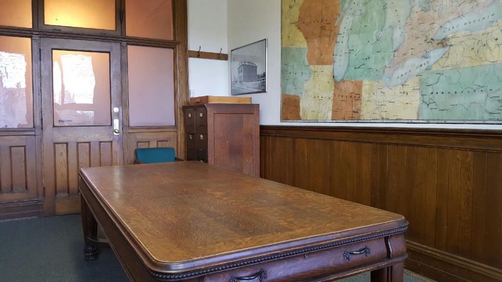 Grande table de travail en bois installée au centre d'une salle lambrissée, positionnée en face de la porte d'entrée. Grande murale illustrant une carte géographique sur la droite.