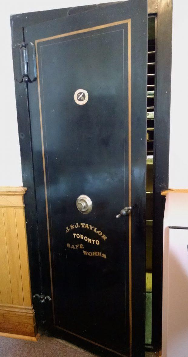Porte noire d'un coffre-fort avec ornementations peintes en or, dont la marque «J. J. Taylor, Toronto, Safe Works» est située sous le cadrant à combinaison et la poignée.