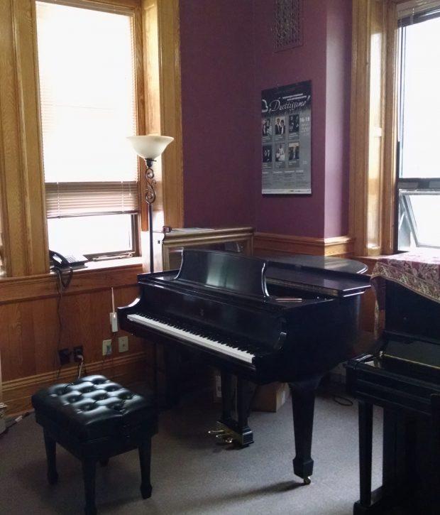 Deux pianos et un banc installés côte-à-côte dans une petite salle peinte de couleur bourgogne, avec de grandes fenêtres; lambrissé, porte et plinthe en chêne; tapis mur à mur.