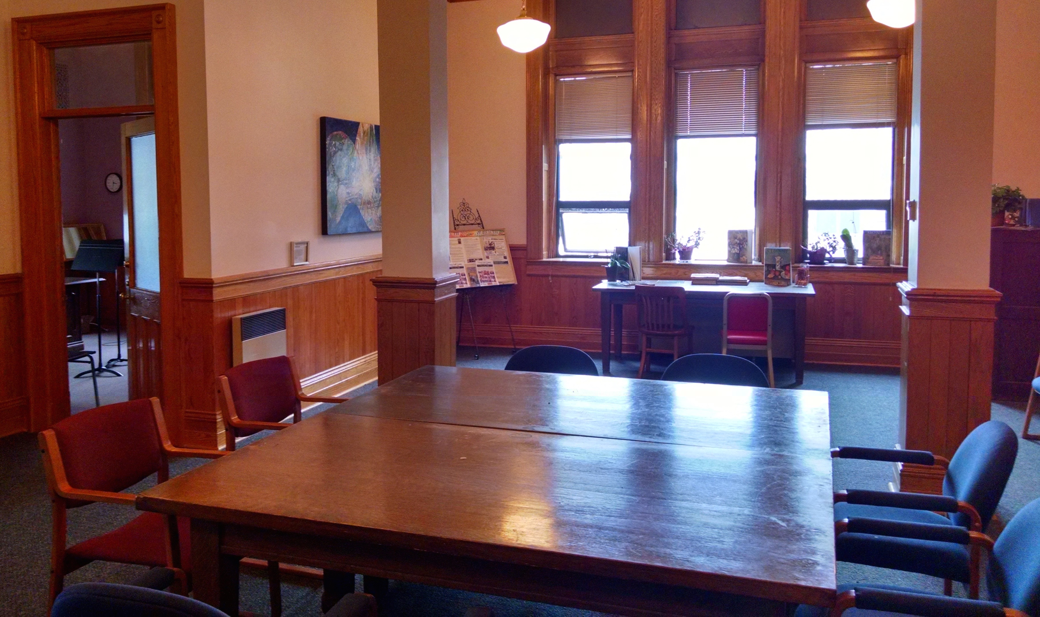 Vue en direction ouest dans la salle d'attente du Conservatoire de musique d'Algoma. Photo prise de la porte d'entrée. Grosses poutres de support au centre de la salle. Large fenêtre directement en face. Porte ouverte à gauche donnant sur un studio ou un bureau. Grande table et chaises au centre de la salle.