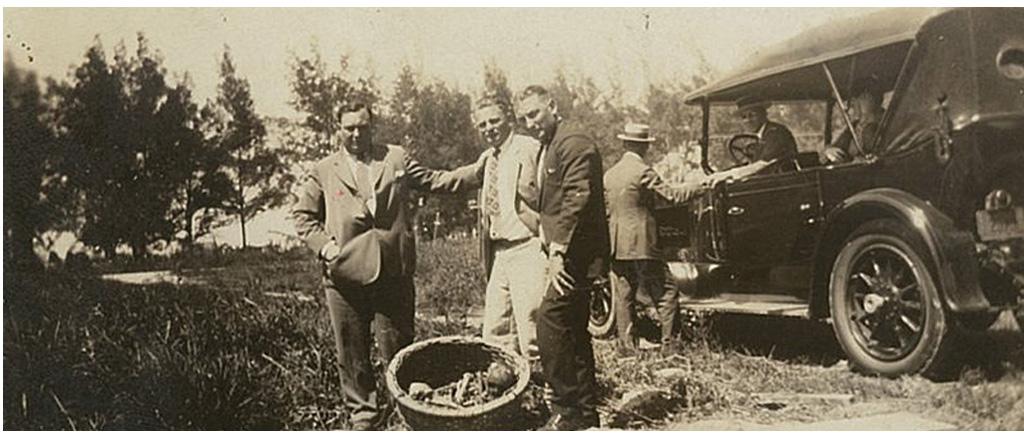 Trois hommes prennent la pose devant une automobile de l'époque