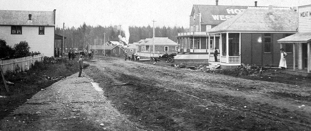 Photographie en noir et blanc d'une large route de terre bordée, de part et d'autre, de bâtiments. On voit, à droite, deux personnes, chacune debout à l'extérieur de l'entrée d'un bâtiment, et à l'arrière, sur la route, un groupe de personnes non loin d'une vieille automobile.
