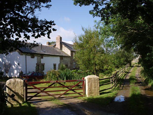 Une route rurale de gravier longe la ferme Bickle. Elle est bordée d'une clôture de bois qui part du grand portail rouge situé devant la maison de campagne. Sur le portail, on peut lire « Lower Whiddon », écrit en lettres blanches.