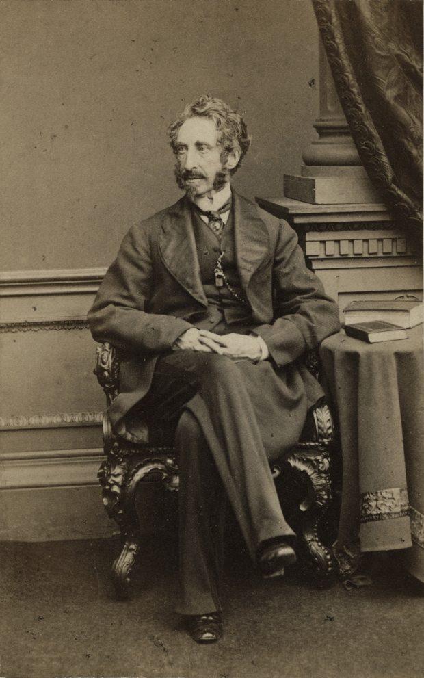 Portrait photo en noir et blanc (réalisé en studio) de Sir Edward Bulwer-Lytton, assis sur une chaise très ornée près d'une petite table où se trouvent deux livres.