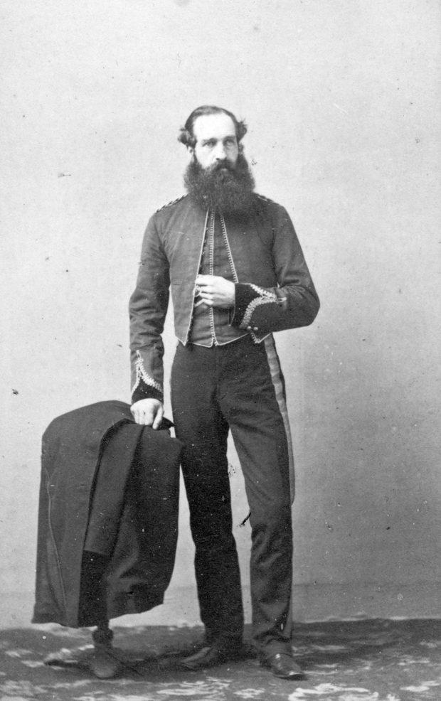 Un portrait en noir et blanc (réalisé en studio) du capitaine Henry Reynolds Luard avec sa longue barbe. Celui-ci porte un uniforme militaire; son bras gauche est replié devant son torse, et sa main droite est placée sur son manteau, qui est drapé sur une petite table.