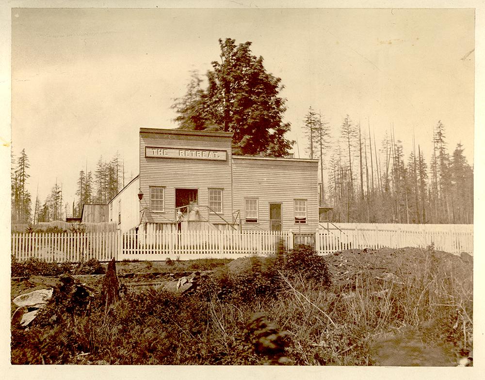 Une photographie monochrome aux tons sépia, prise autour de 1865, d'un bâtiment à deux devantures. À gauche, on voit un saloon qui a une fausse façade plus haute portant une enseigne où l'on peut lire « The Retreat ». Chaque devanture a sa propre porte et une fenêtre de part et d'autre de la porte. Il y a une clôture en lattis devant le bâtiment et une forêt à l'arrière-plan.