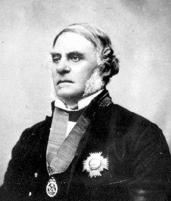 Portrait photo en noir et blanc (réalisé en studio) du gouverneur James Douglas portant une médaille à son cou et un insigne richement décoré sur sa veste.