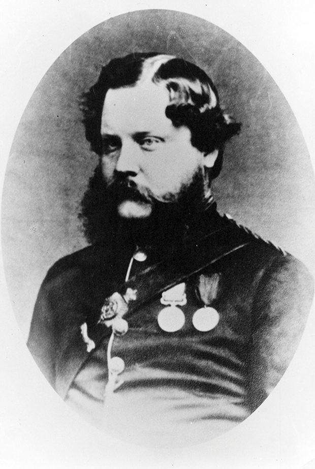 Portrait en noir et blanc ovale du docteur John Vernon Seddall, vêtu d'une tenue militaire officielle et portant diverses médailles et marques de distinction sur la poitrine. Il a les cheveux luisants avec une raie sur le côté et une barbe fournie.