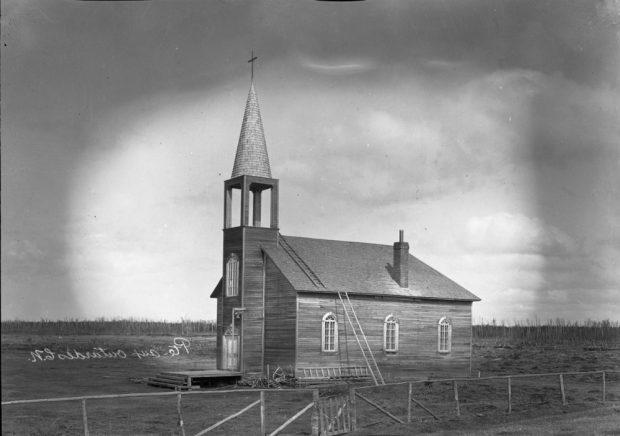 Photo en noir et blanc d'une église en bois dans une plaine.