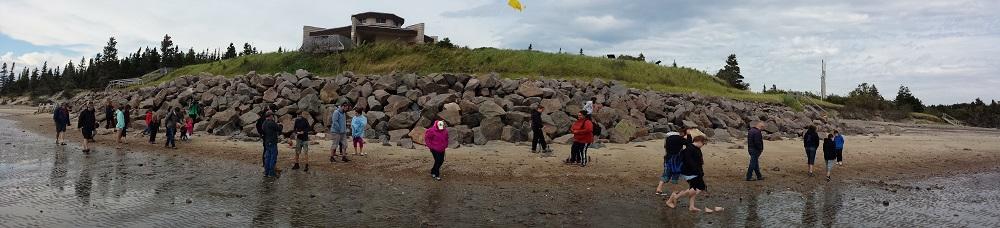 Plusieurs personnes marchant le long de la plage en contrebas d'un bâtiment