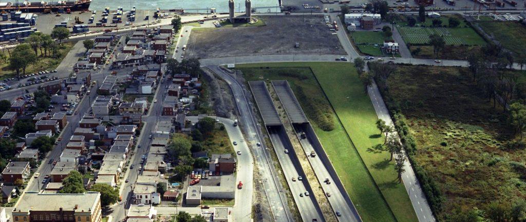 Des voitures circulant sur une autoroute avec des installations portuaires et un cours d'eau en arrière plan