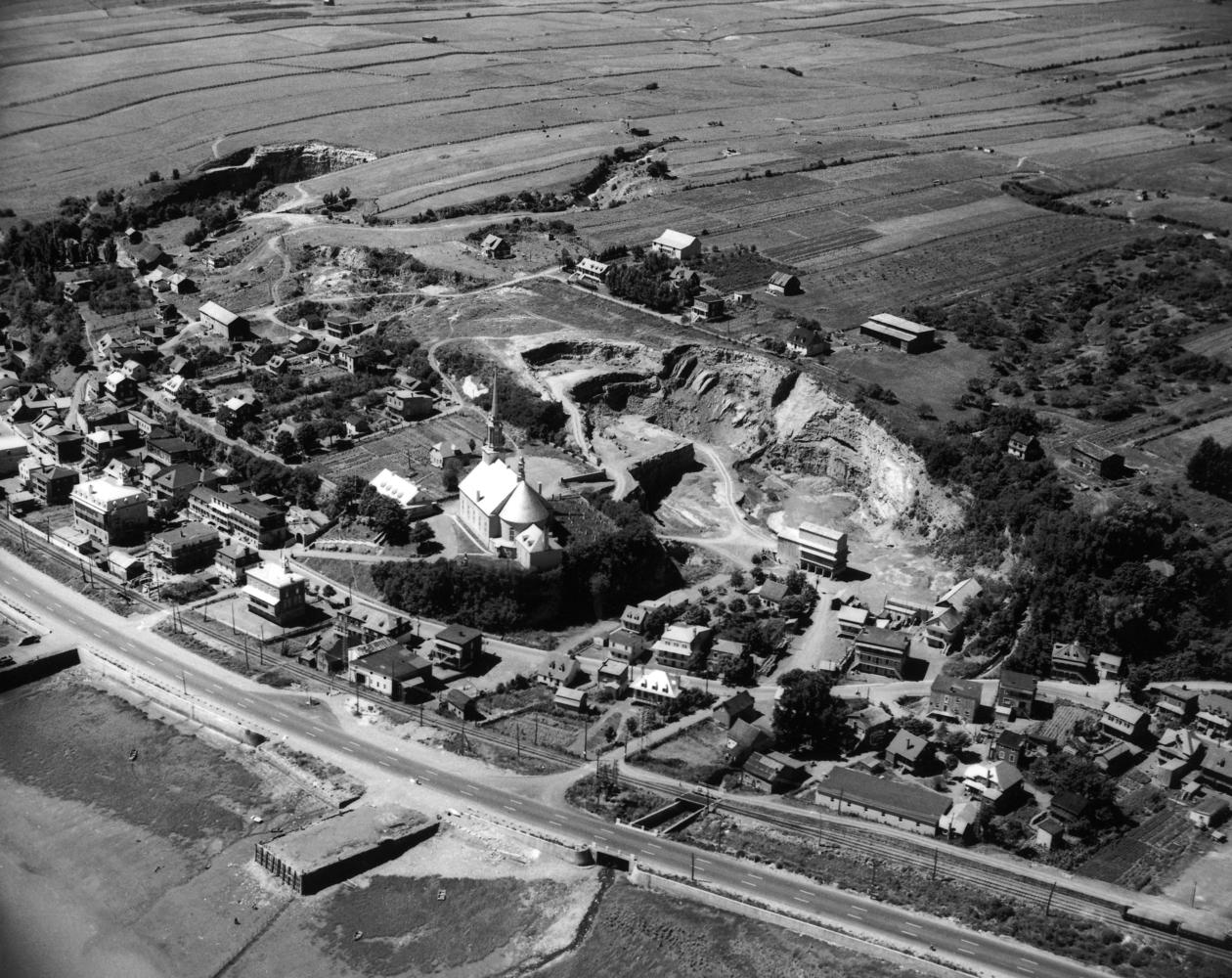 Photographie d'archives en noir et blanc. La municipalité de Château-Richer se déploie autour de l'église, qui se trouve au centre de l'image. Outre des maisons, on aperçoit une carrière de pierre, des champs cultivés, un chemin de fer et le boulevard Sainte-Anne.