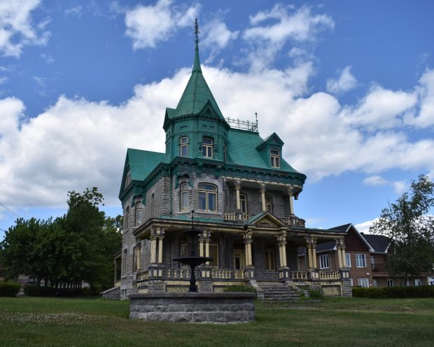 Photographie couleur d'une grande maison en pierre à trois étages au centre d'un terrain gazonné. Le toit de la demeure est vert. La façade présente un balcon au premier étage et une véranda au rez-de-chaussée. Les cadres de fenêtre, les colonnes et les balustrades sont peints en jaune. Une fontaine se trouve devant la maison. En arrière-plan, on aperçoit des arbres et une maison voisine.