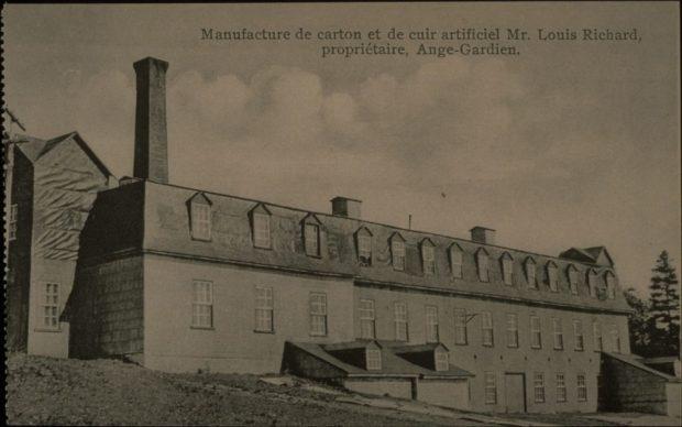 Photographie d'archives en noir et blanc montrant une vue de trois-quarts d'un bâtiment industriel à trois étages percés de multiples fenêtres et à toit mansardé. Une longue cheminée se dresse à l'arrière gauche du bâtiment. Deux cheminées moins hautes s'élèvent au centre de l'édifice.