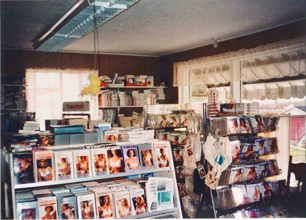 Photographie couleur montrant des étalages dans un magasin. On y voit des emballages de soutien-gorge et d'autres sous-vêtements sur des présentoirs de plancher et dans des étagères murales. Deux fenêtres laissent entrer la lumière de l'extérieur.