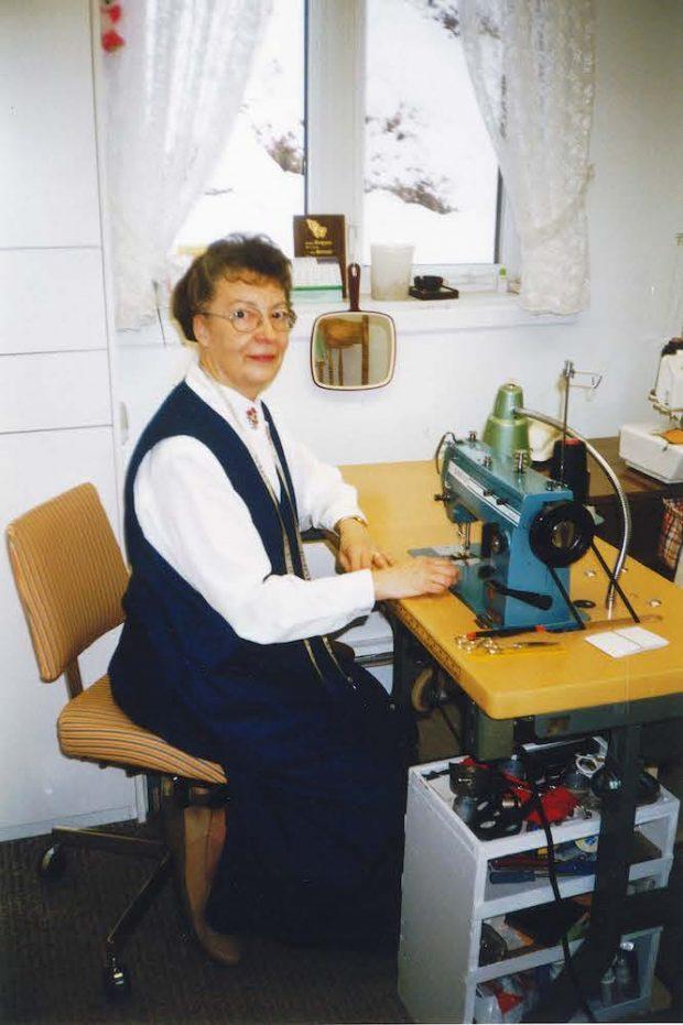 Photographie couleur de Marie-Rose Jalbert assise à sa machine à coudre, devant une fenêtre. Elle porte un ruban à mesurer autour du cou. On voit des accessoires de couture, un miroir et une lampe autour de son plan de travail.