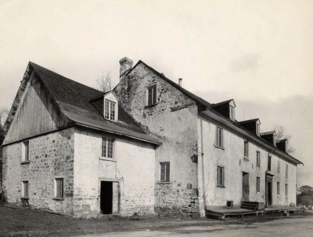 Photographie d'archives en noir et blanc montrant une vue éloignée de la façade et du profil gauche d'un édifice à pignons à trois étages. Le bâtiment est en pierre partiellement recouverte de chaux. Une annexe de plus petites dimensions se trouve à la gauche.