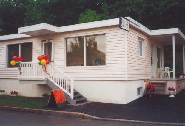 Photographie couleur d'une maison rose pâle à un étage. La vue de trois-quarts montre deux portes d'entrée, une sur le côté et une à l'avant. Sur le côté de la maison, on voit des chaises blanches sur la petite galerie et des fleurs rouges en pot en/au bas des escaliers. À l'avant, des ballons rouges, jaunes, verts et bleus sont accrochés à la balustrade de la galerie. À côté de l'escalier situé à l'avant, une affiche orangée indique « Soutien-gorge - 20% ». Une enseigne où on lit « Salon Marie-Rose » est accrochée perpendiculairement à la façade, de façon à être visible de la rue.