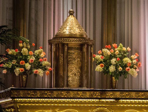 Photographie couleur d'un tabernacle cylindrique en métal repoussé richement travaillé qui est déposé sur un autel entre deux grands vases contenant des bouquets de fleurs roses et blanches. Le haut du tabernacle est de forme conique.