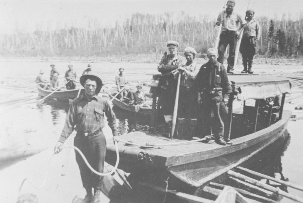 Plusieurs hommes se tiennent dans des embarcations sur une rivière où flottent plusieurs billots de bois.