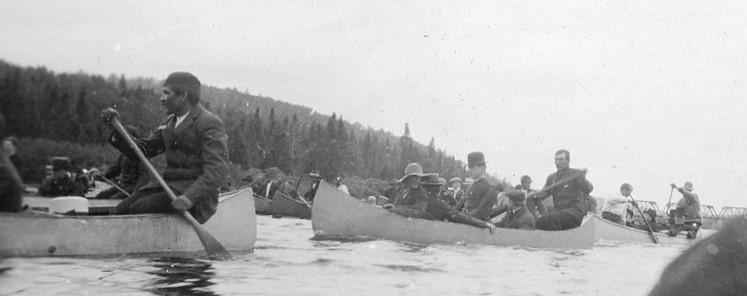 Plusieurs canots remplis d'hommes glissent sur la rivière.