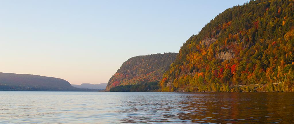 La rivière Saint-Maurice défile entre de hautes falaises couvertes d'arbres teintés des couleurs automnales.