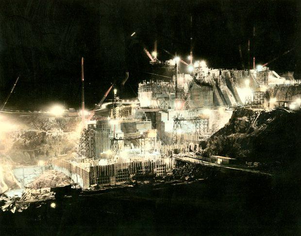 Site d'un barrage en construction. Les immenses grues et les échafaudages sont éclairée par des projecteurs.