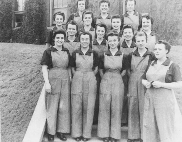 Un groupe de femmes en habit de travail pose devant un immeuble en brique