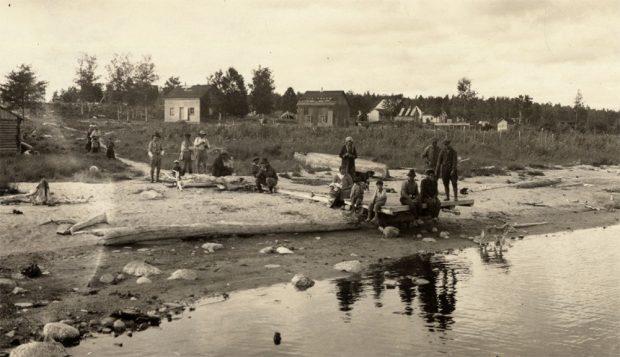 Un groupe de personnes se tient sur une plage. Derrière eux, de modestes maisons en bois sont dispersées.